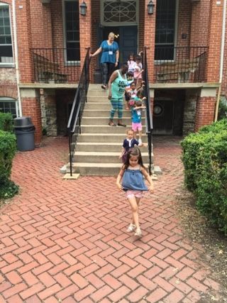 a group of children descending stairs after class