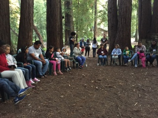 a circle of participants sit in the forest praying