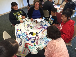 a group of children and an adult sitting around a quilt project
